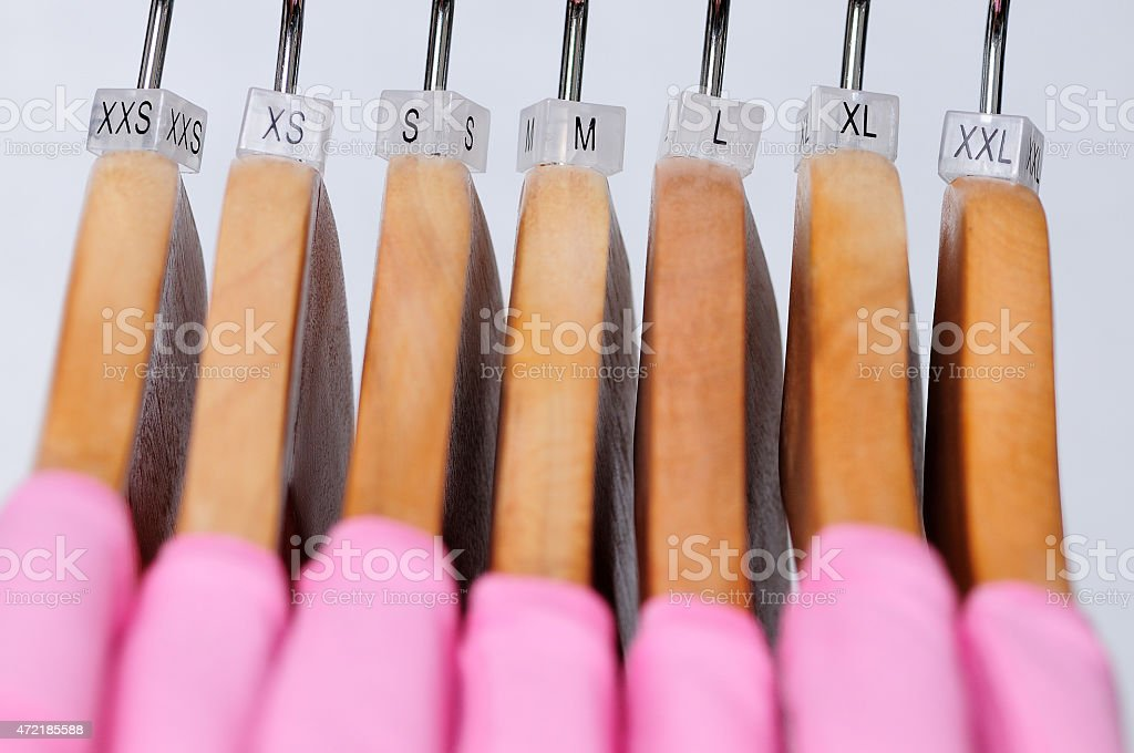 Pink women's t-shirts of various sizes hanging on wooden hangers stock photo