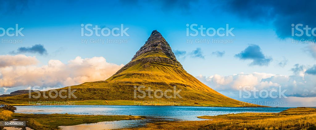 Pinnacle mountain peak panorama soaring above ocean fjord Kirkjufell Iceland stock photo