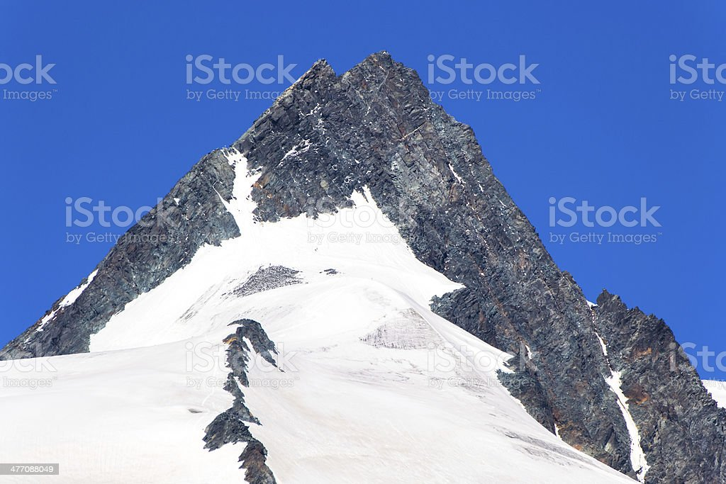 pinnacle with snow beneath and a clear blue sky above stock photo