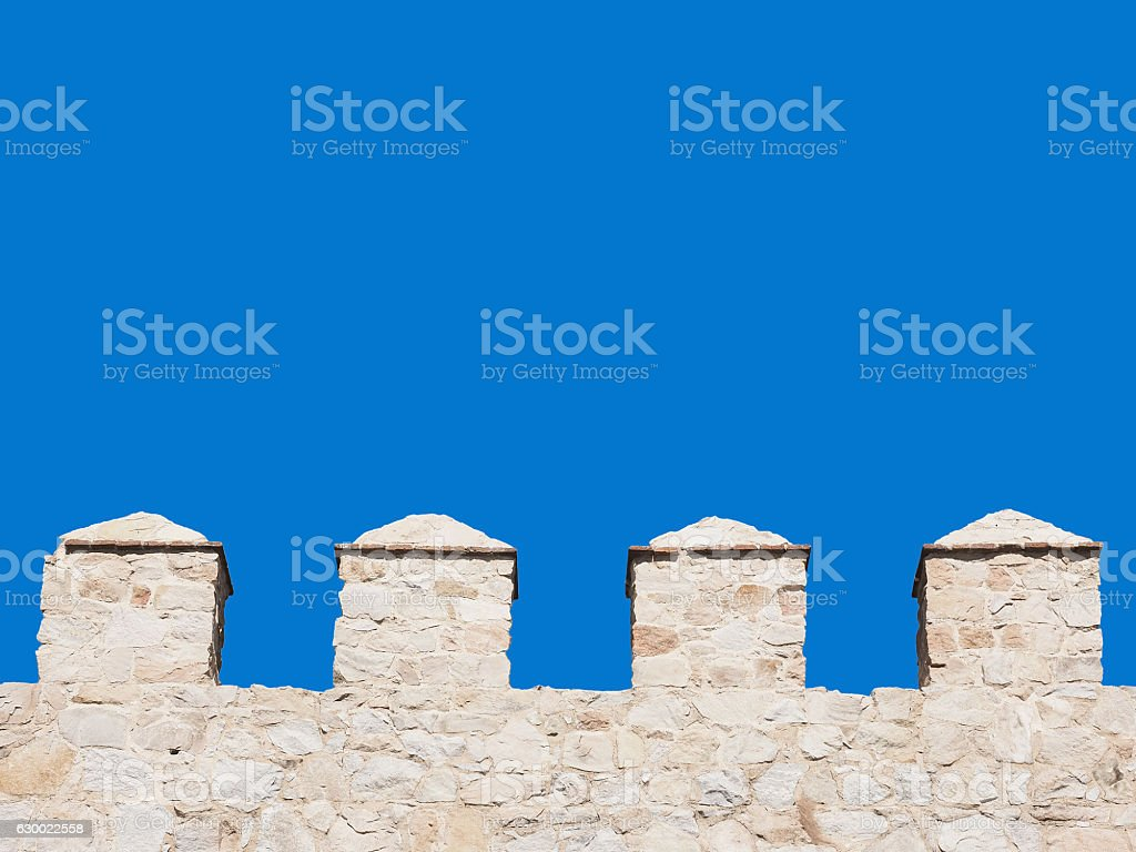 pinnacles of a wall isolated on blue sky stock photo