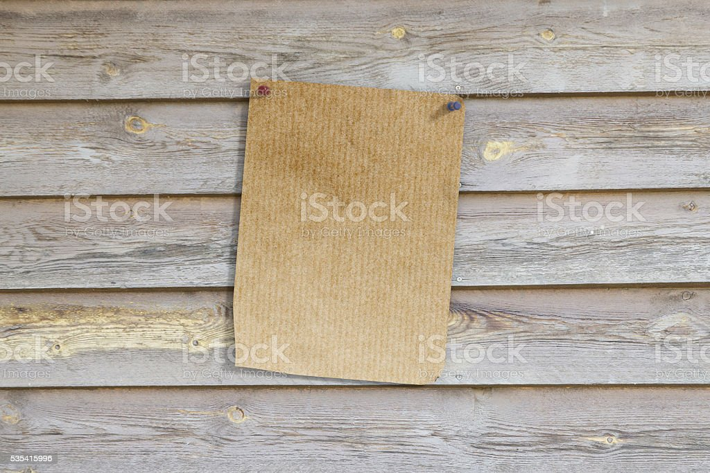 Pinned page on wooden wall stock photo