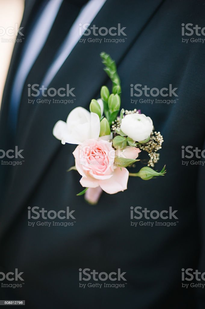 Pinning a Boutonniere for groom stock photo