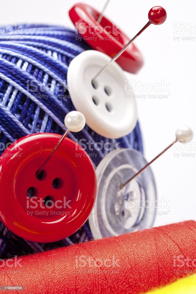 pins in wool ball with buttons stock photo