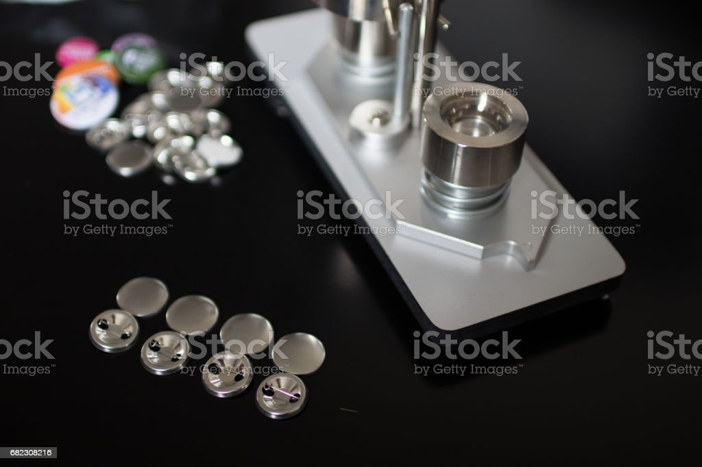 Pins press machine with empty pins and ready pins. Press button maker for 2,5 cm badge. stock photo