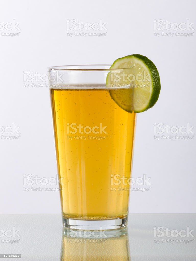 Pint Glass of Beer with Lime and Reflection stock photo