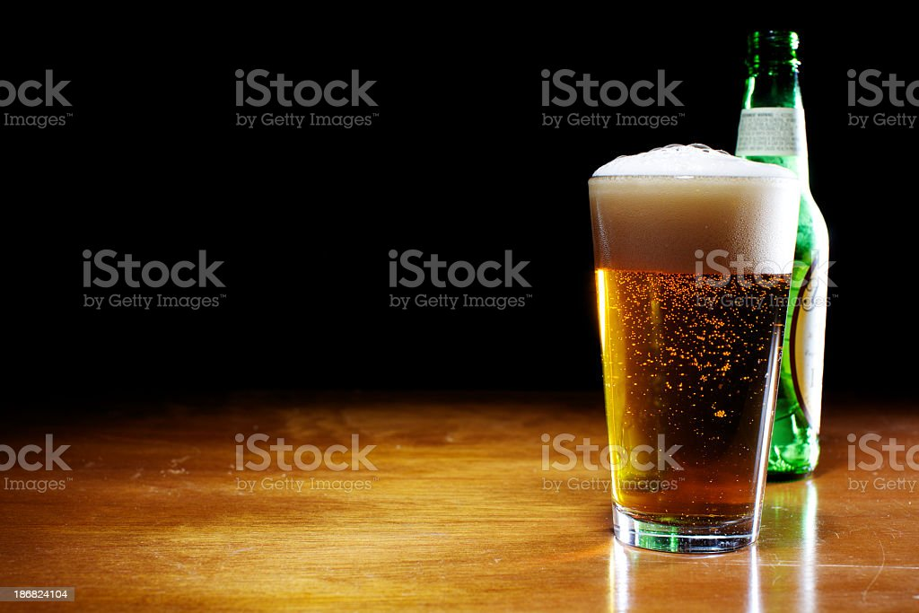 A pint of beer next to a bottle on a wooden table royalty-free stock photo