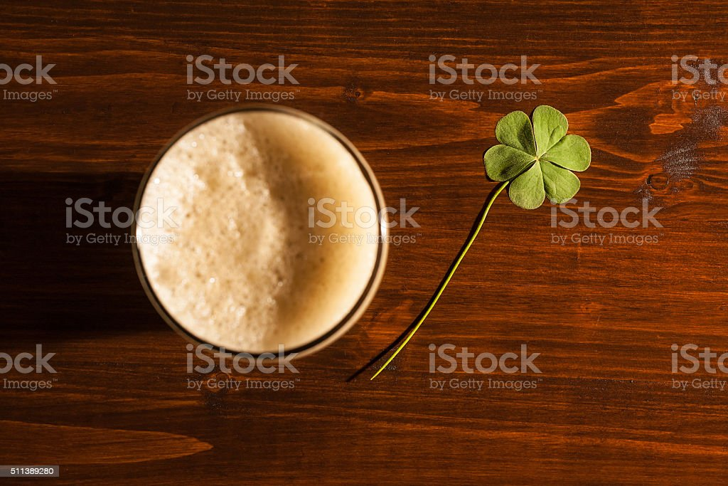 Pint of black beer and a shamrock stock photo