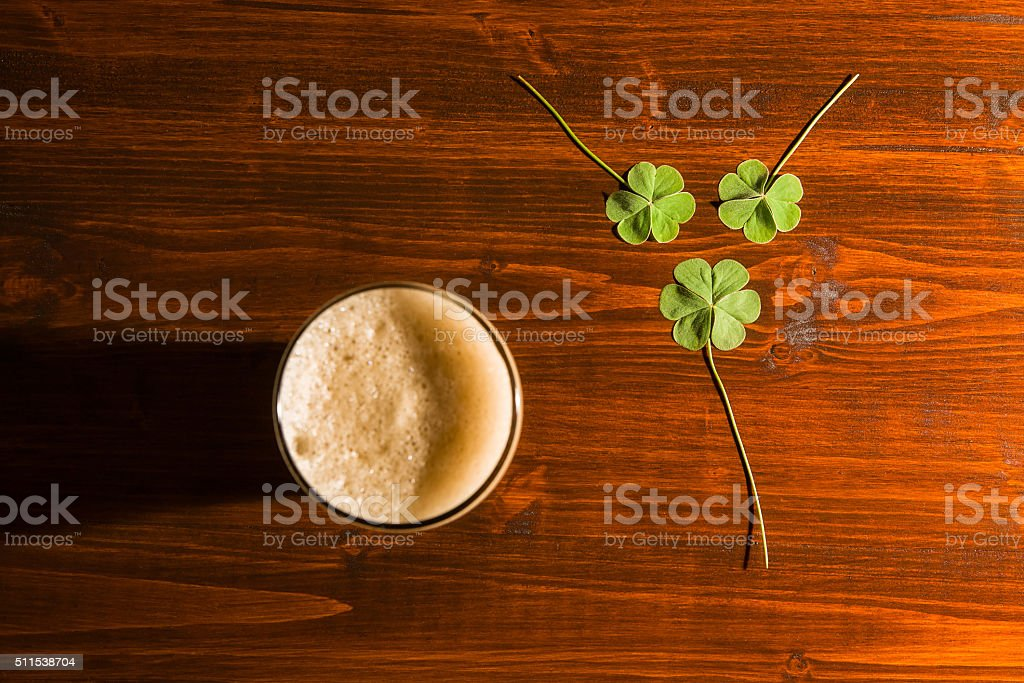 Pint of black beer and three shamrocks stock photo