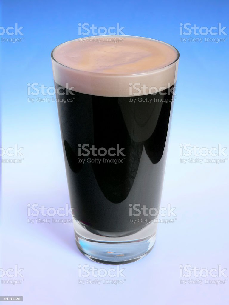 Pint Of Stout beer on blue colored background stock photo