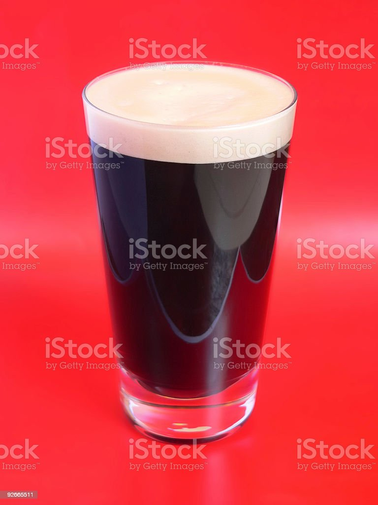 Pint Of Stout beer on red colored background stock photo