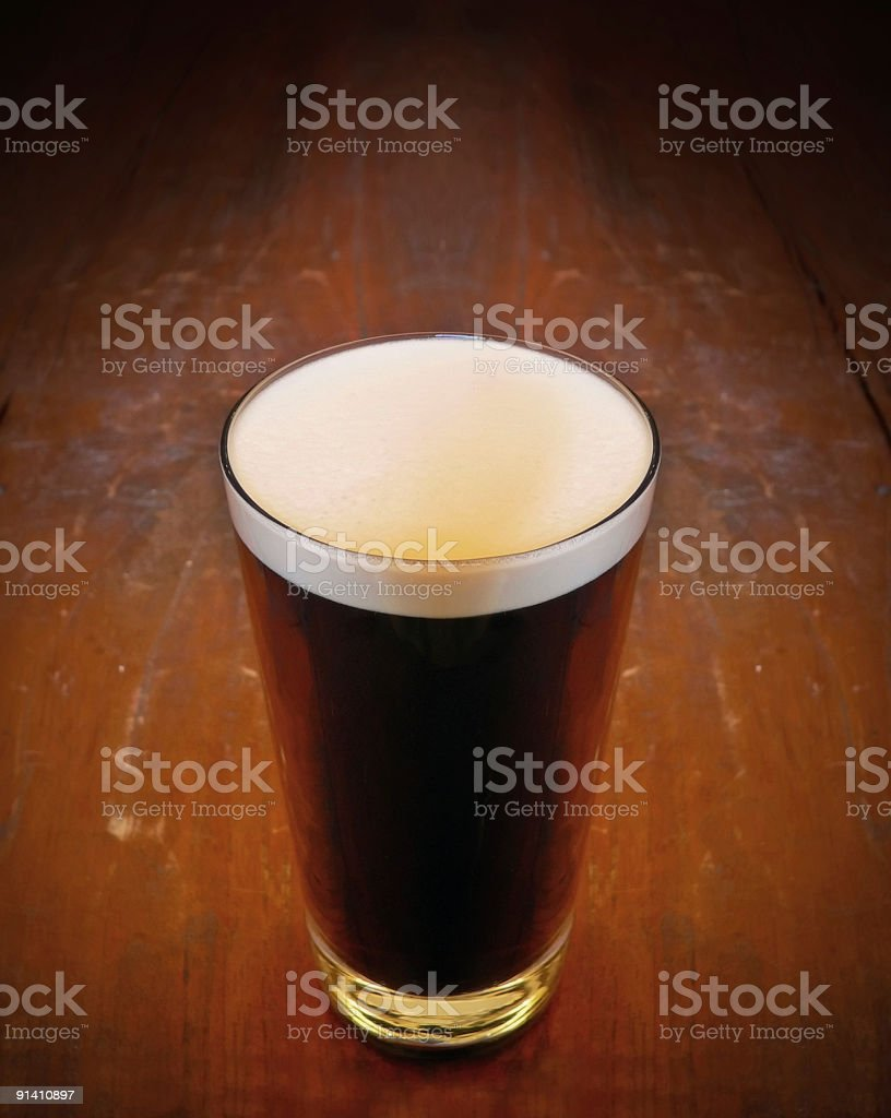 Pint Of Stout beer on wooden bar counter stock photo