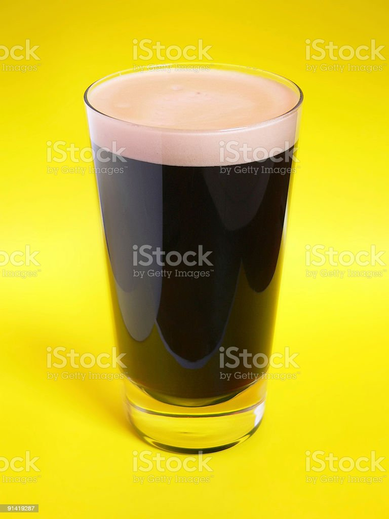 Pint Of Stout beer on yellow colored background stock photo