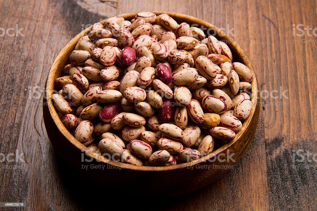 pinto beans on wood bowl stock photo