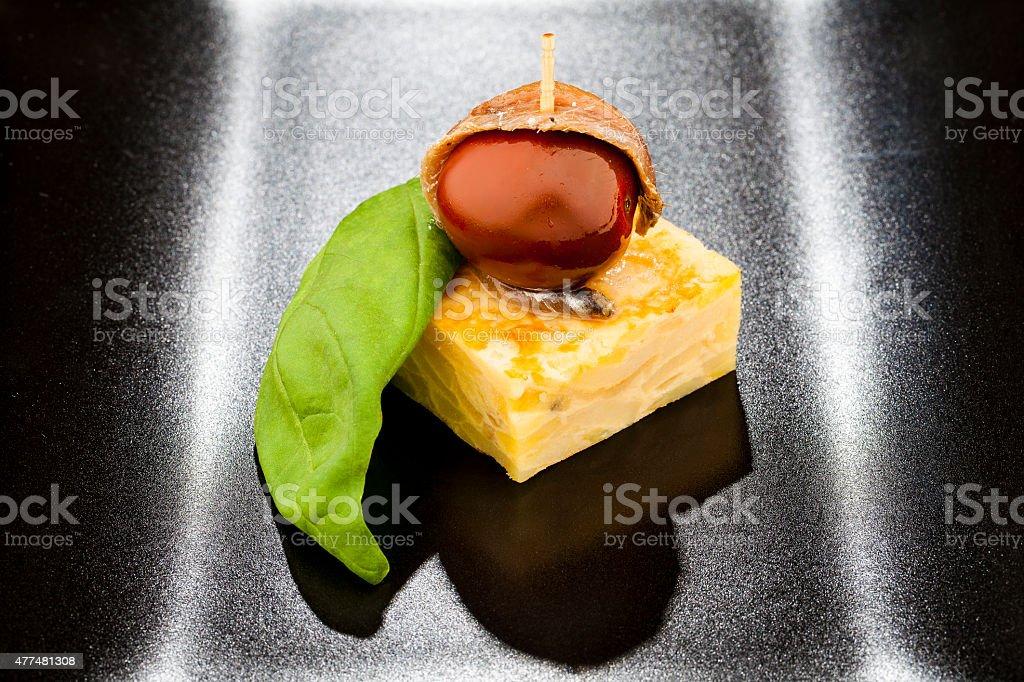 Pintxo de tortilla, tomate y anchoa con albahaca stock photo
