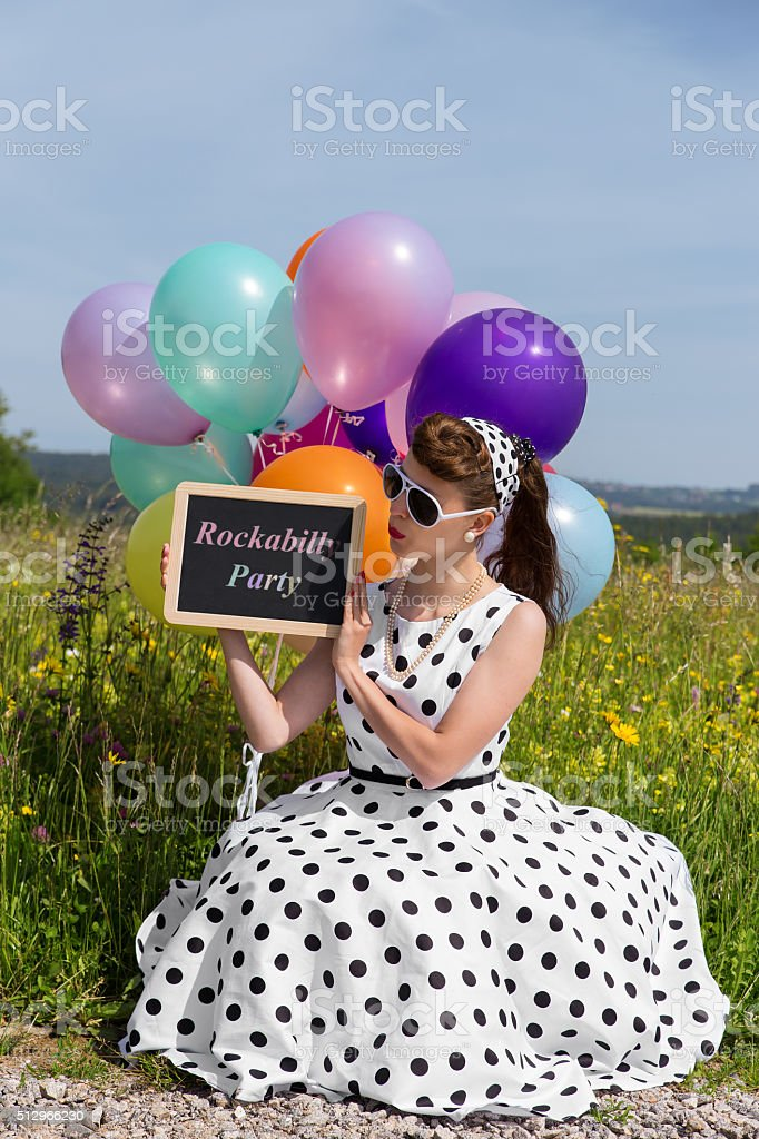 Pinup Girl holding a slate with text Rockabilly Party stock photo