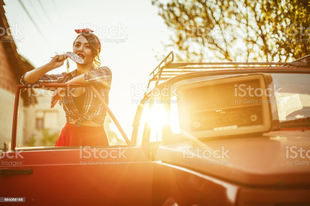 Pin-up girl in the old timer vintage car stock photo
