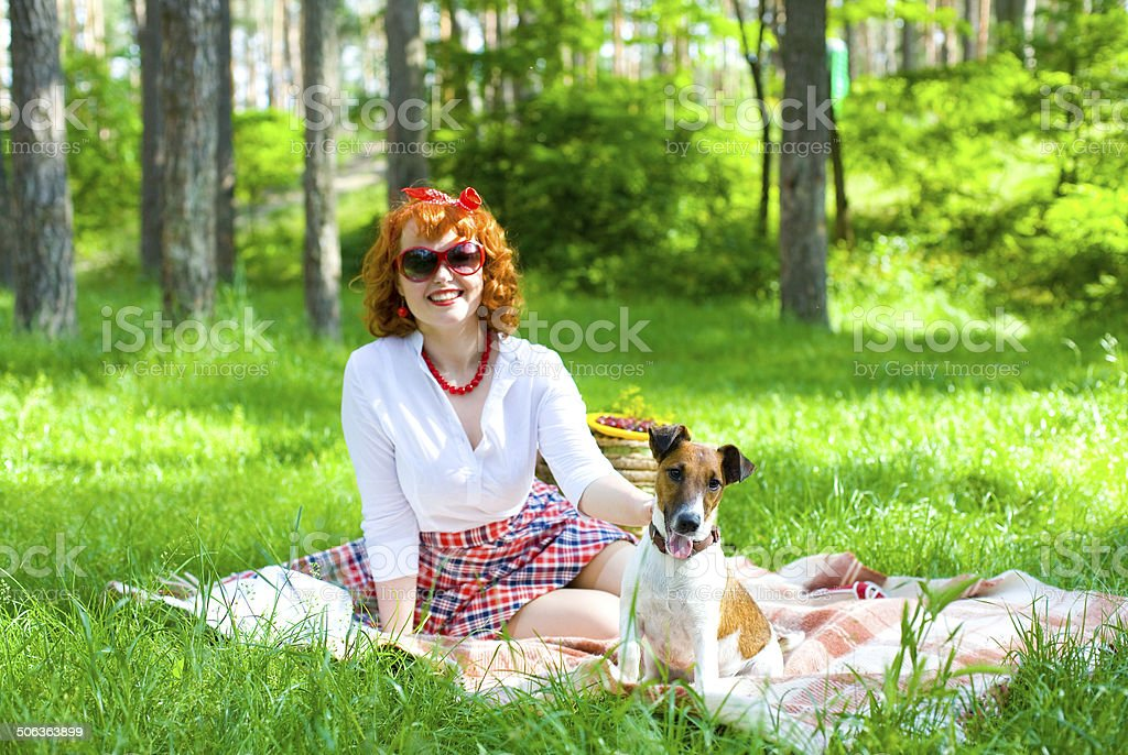 Pin-up girl playing with her dog on lawn stock photo
