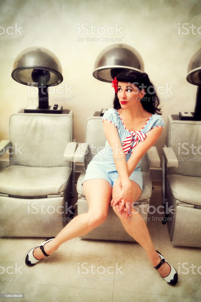 Pin-up girl: sexy woman in a beauty salon with hairdryers royalty-free stock photo
