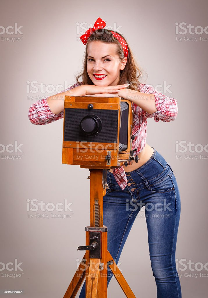 Pin-up girl with retro wooden camera stock photo