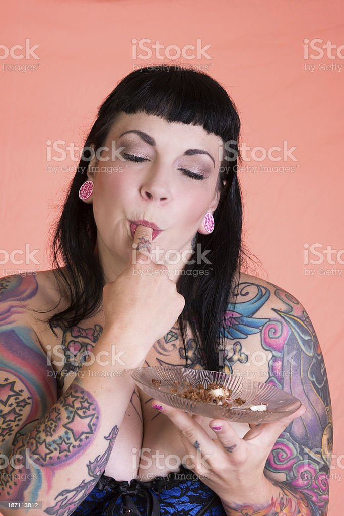 Pinup model, eyes closed sucking crumbs off finger. royalty-free stock photo
