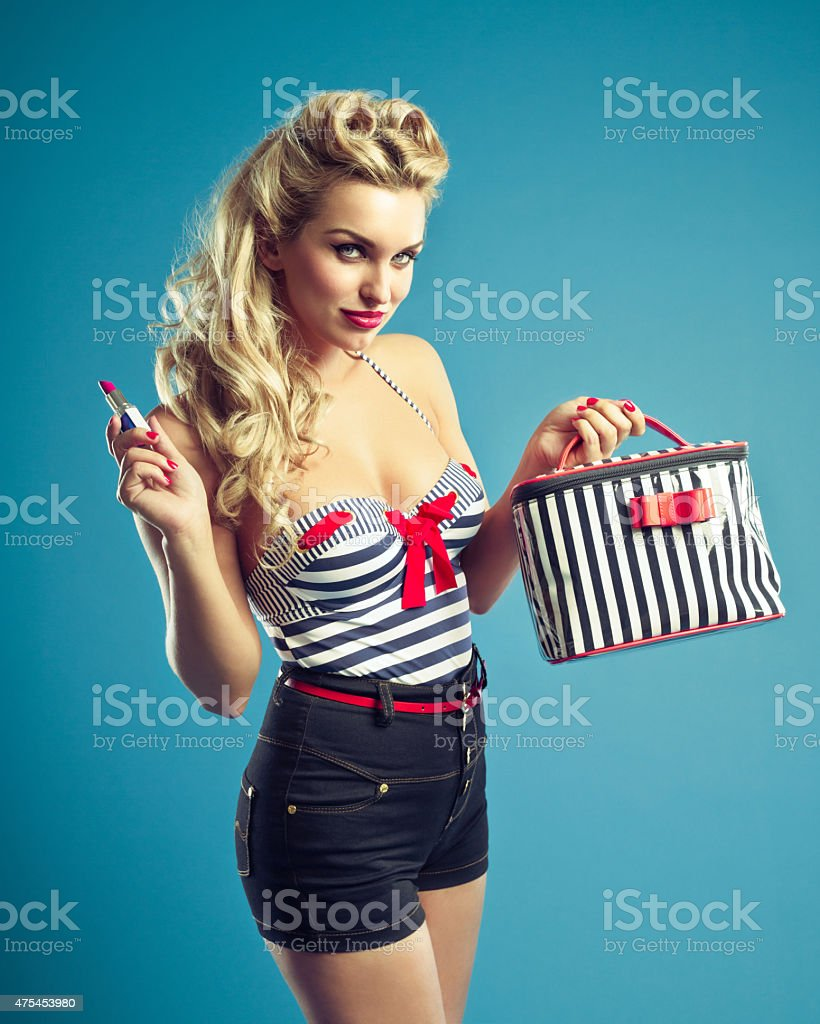 Pin-up style sailor blonde woman holding lipstick stock photo