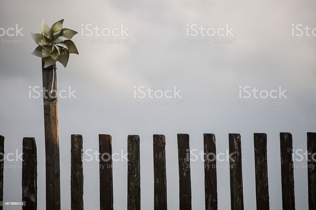 Pinwheel attached to old wooden fence. stock photo