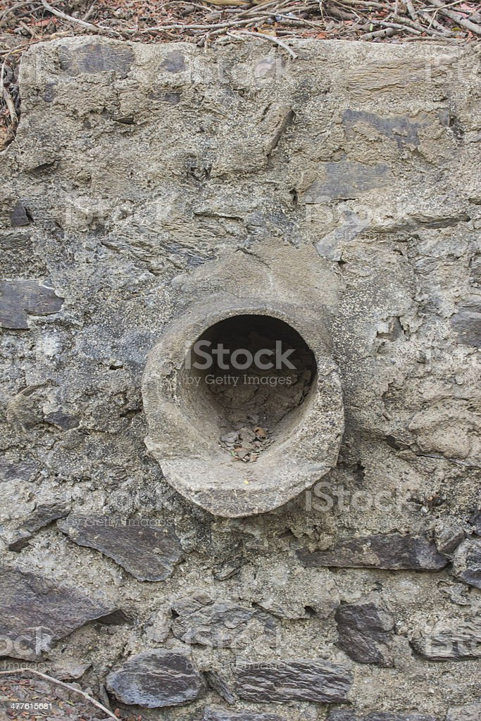 Pipe in old stone wall royalty-free stock photo
