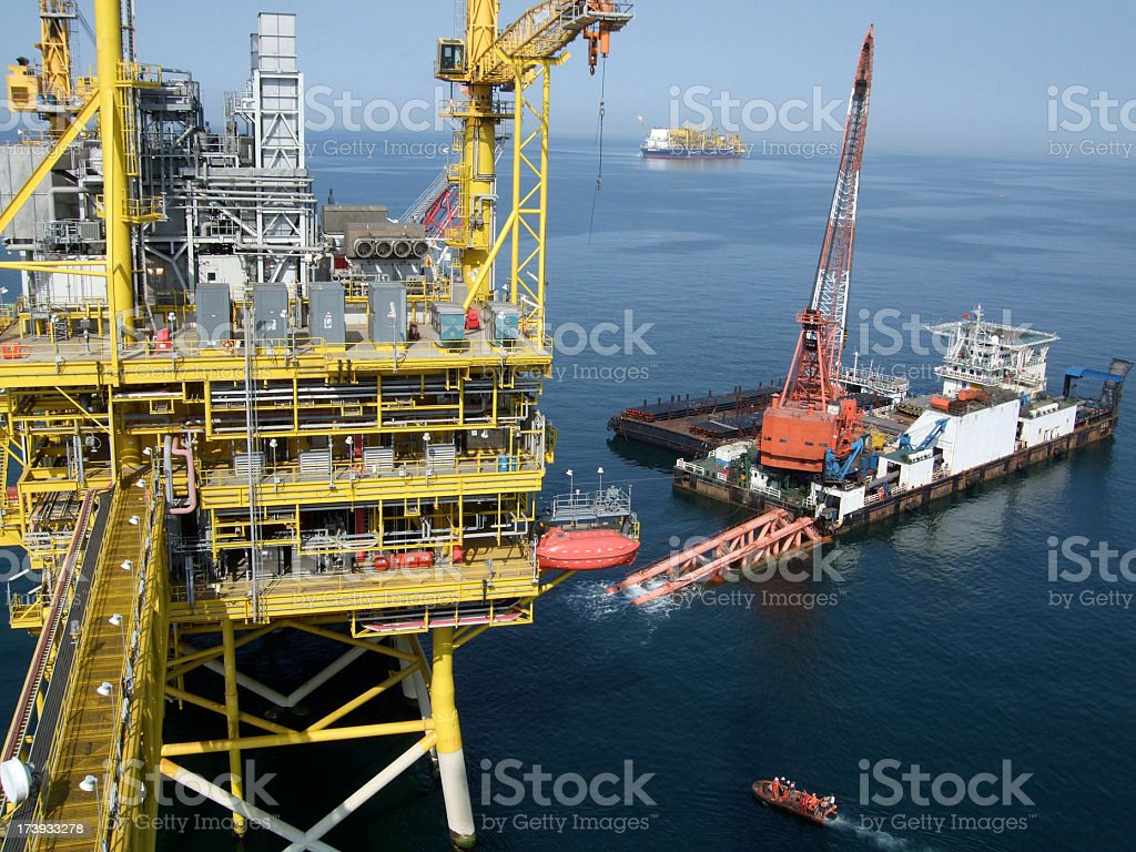 Pipe laying barge by oilrig stock photo