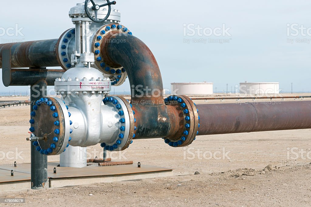 Pipelines and storage tanks in oil field stock photo