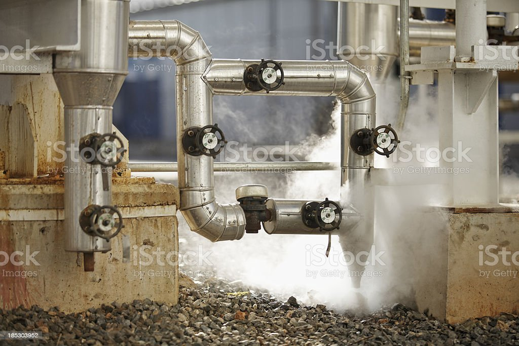 pipelines emitting steam at industrial site stock photo