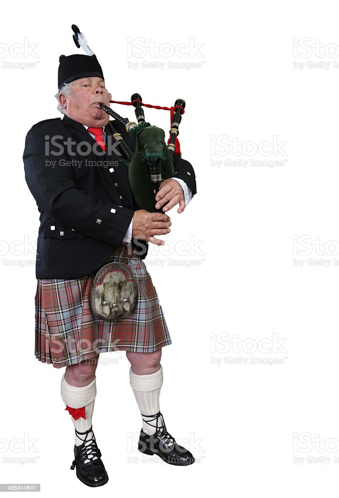 Piper playing the bagpipes in full Scottish Dress - isolated. stock photo