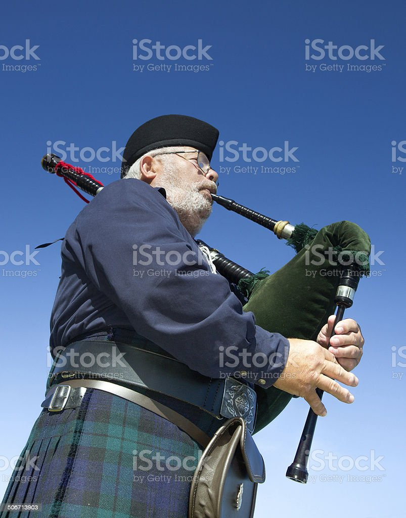 Piper playing the bagpipes in Scottish kilt against blue sky stock photo