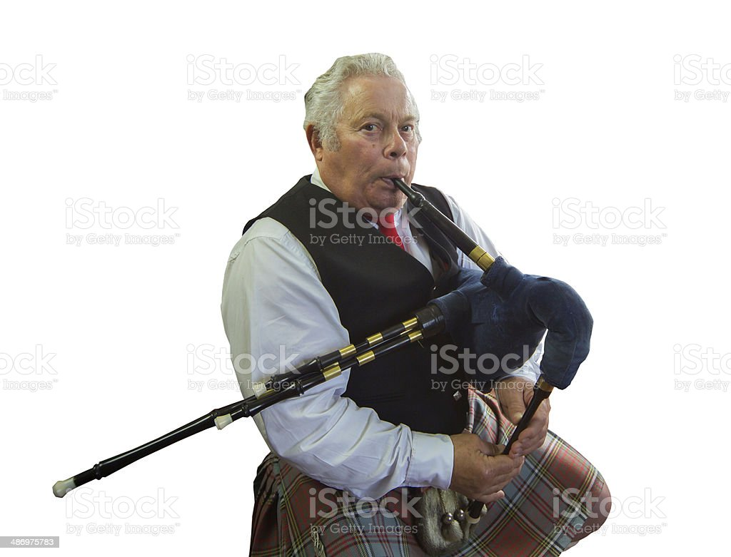 Piper playing the bagpipes in Scottish kilt seated - isolated. stock photo