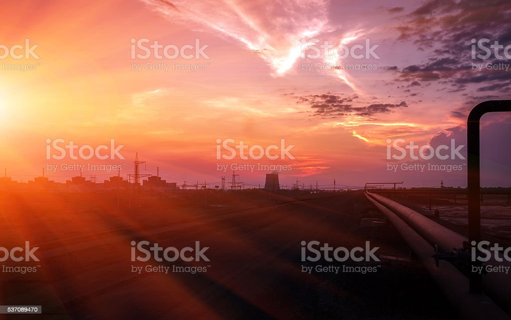 pipes and power lines against a red sunset. stock photo