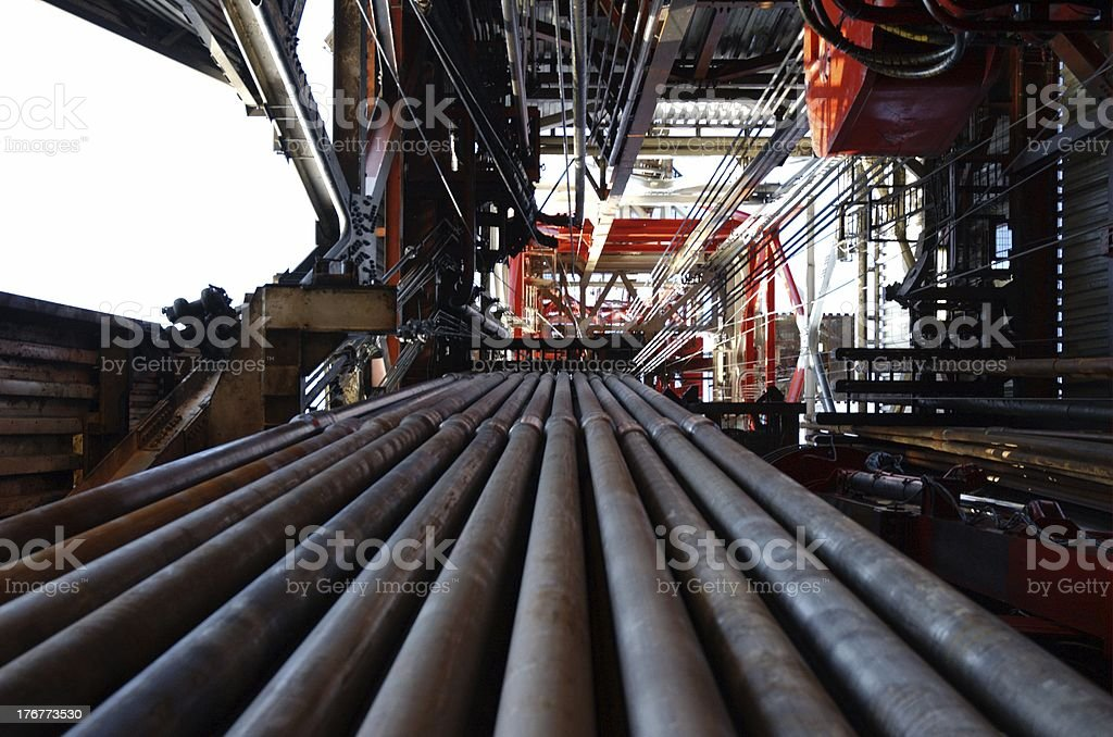 Pipes in rack on offshore oil rig looking up inside derrick stock photo