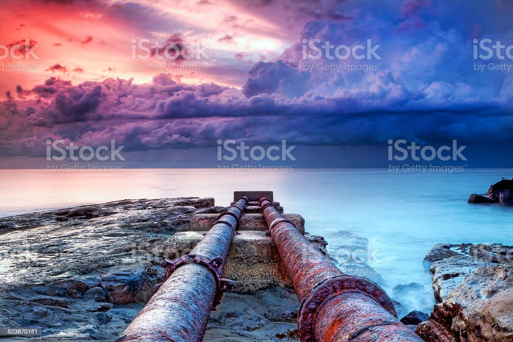 Pipes leading into the ocean stock photo