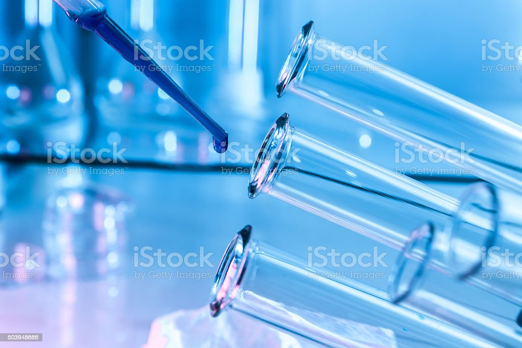 Pipette adding fluid to one of several test tubes .medical stock photo