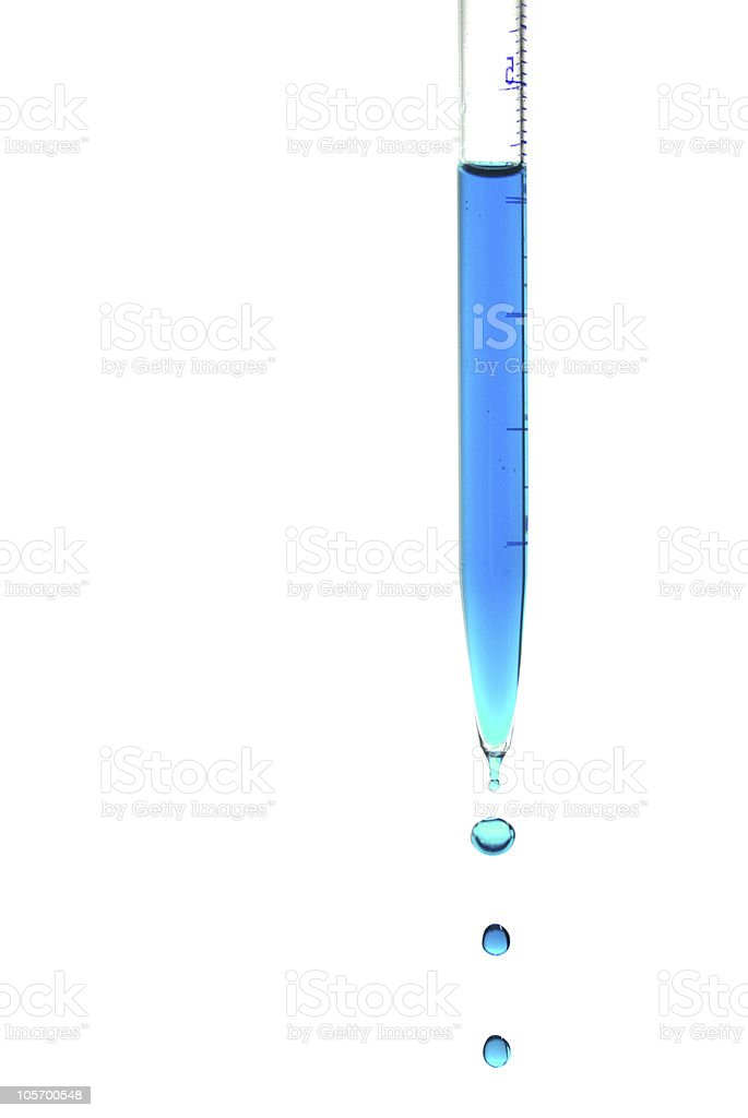 A pipette dripping blue liquid drops one at a time stock photo