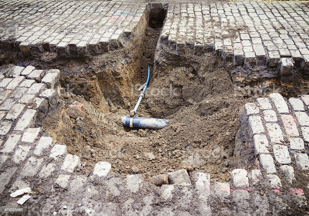 Pipework under cobbles stock photo