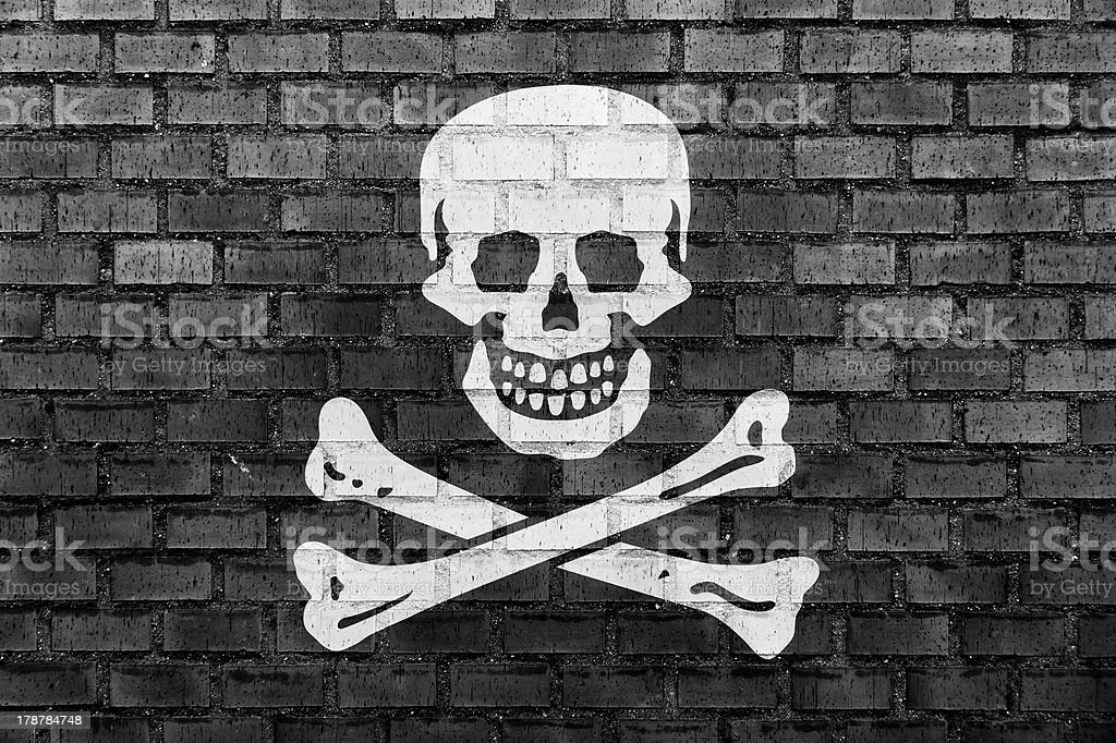 Pirate flag on a brick wall stock photo