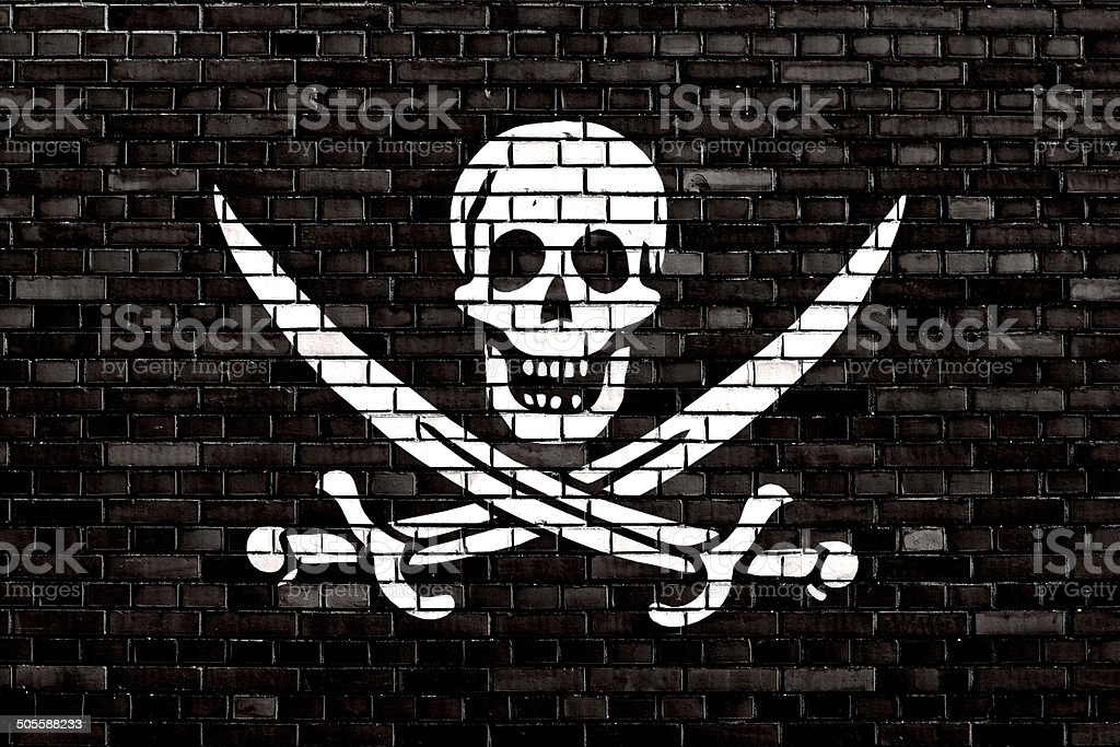 Pirate flag painted on brick wall stock photo