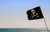 pirate flag waving with blue sea background