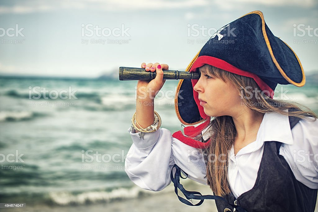 Pirate girl looking with spyglass stock photo