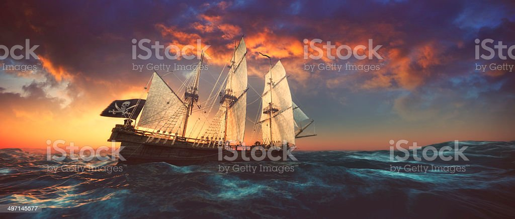 Pirate ship sailing on the open seas at sunset stock photo