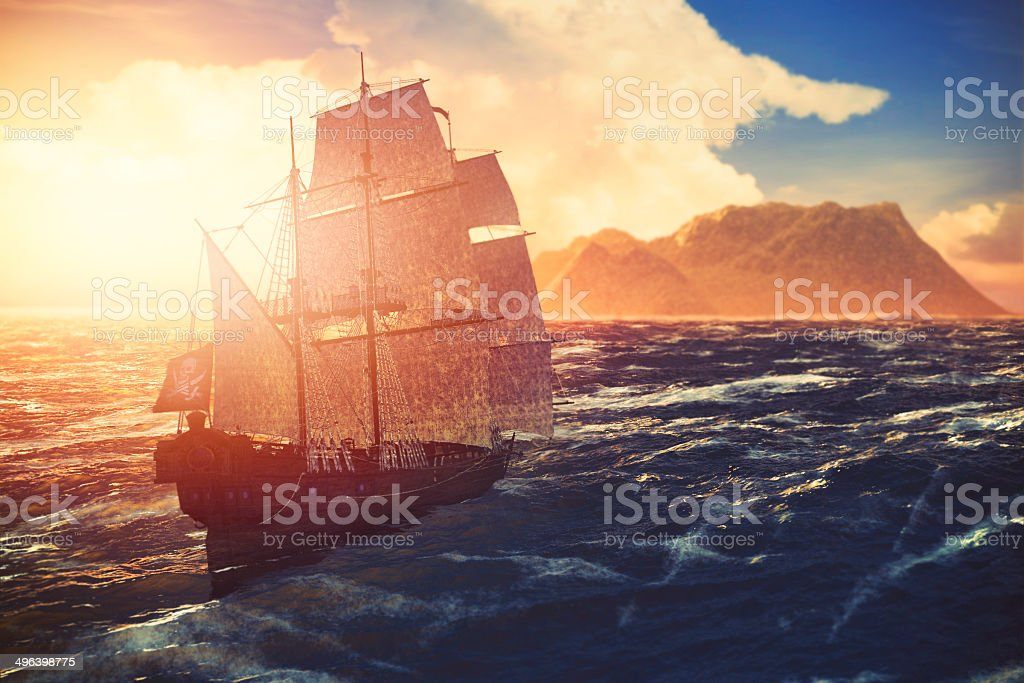 Pirate ship sailing towards lonely island at sunset stock photo