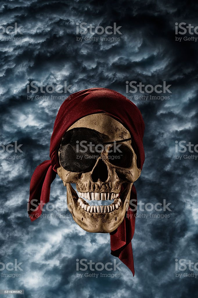 Pirate Skull wearing a red bandanna against dark gloomy clouds stock photo