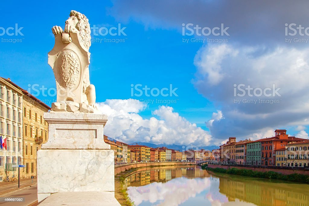 Pisa, Arno river, lion statue and buildings reflection. Lungarno stock photo