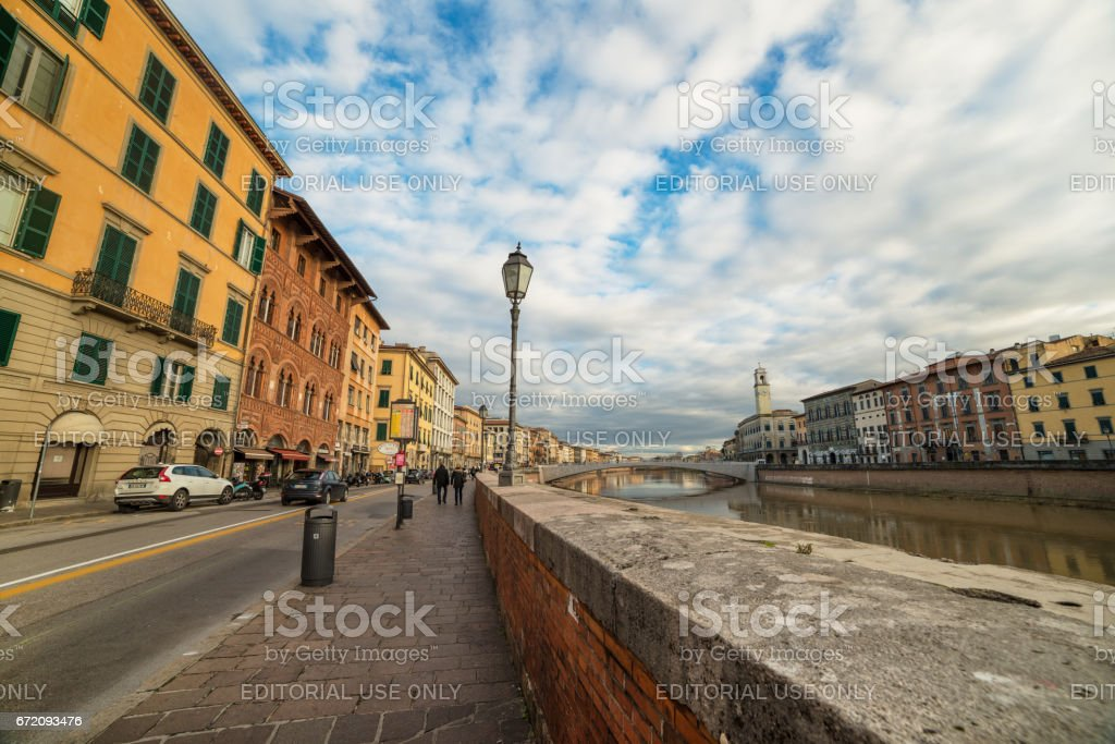 Pisa - September 2012, Tuscany, Italy: Street view of Lungarno Antonio Pacinotti, view on Arno river at the evening time, promenade in the old city center, wide angle photography stock photo