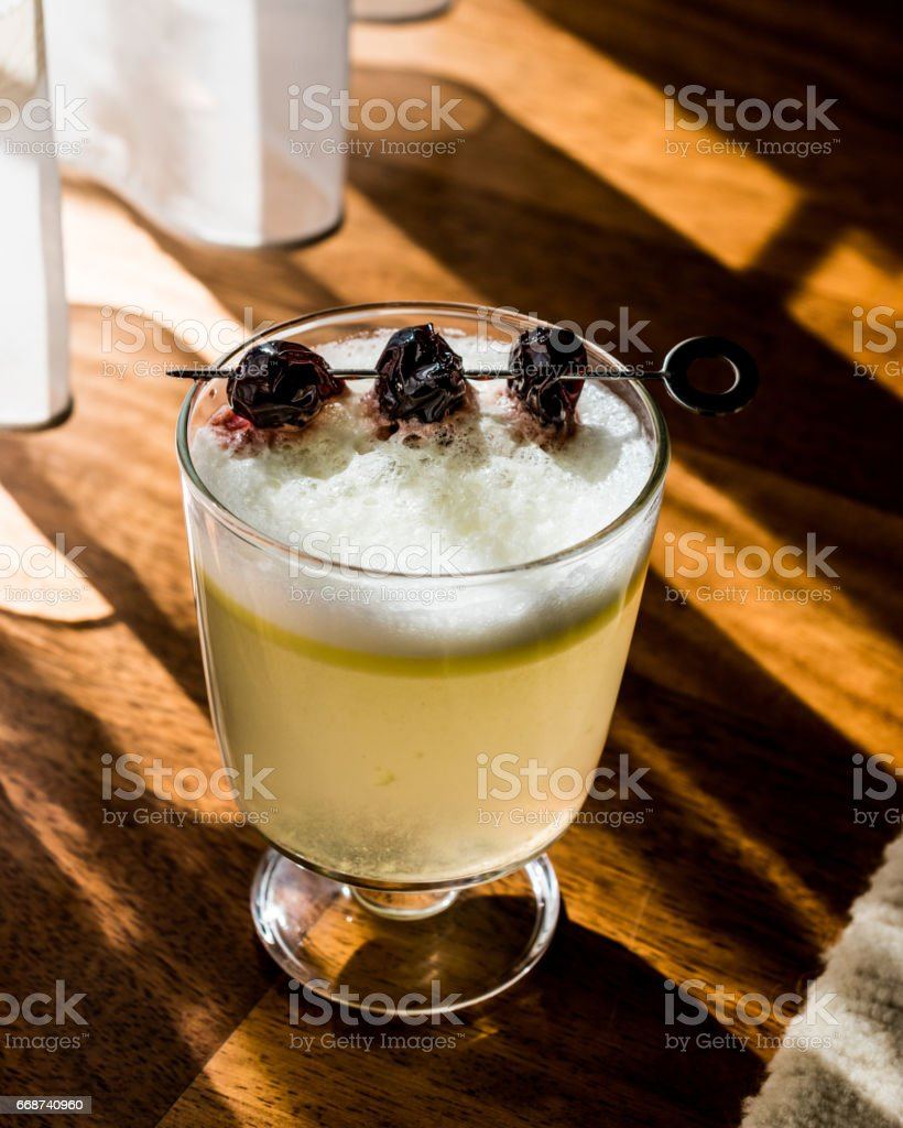 Pisco Sour Cocktail with cherry (natural light). stock photo