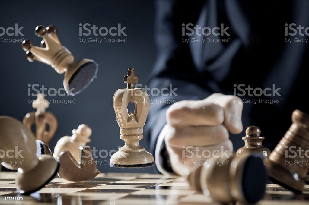 Pissed off chess player is punching in the chessboard stock photo